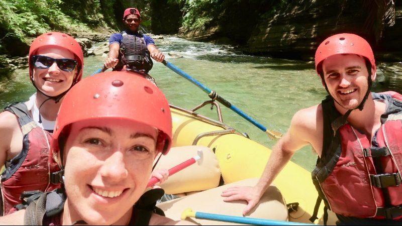 People wearing red helmets while rafting