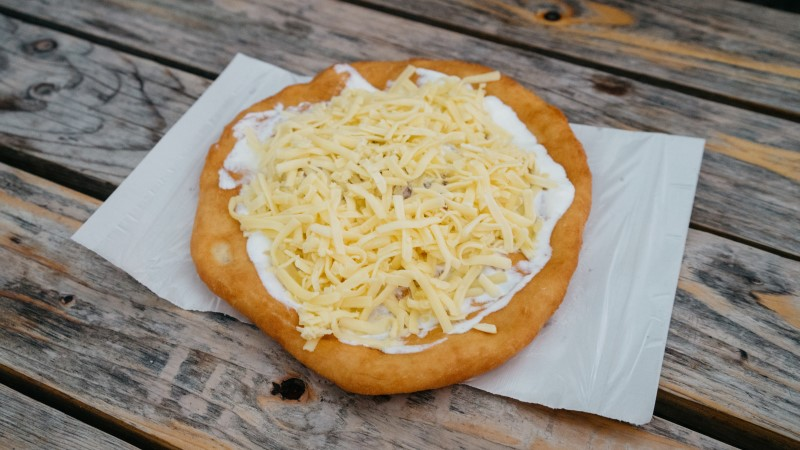 Langos topped with cheese and sour cream