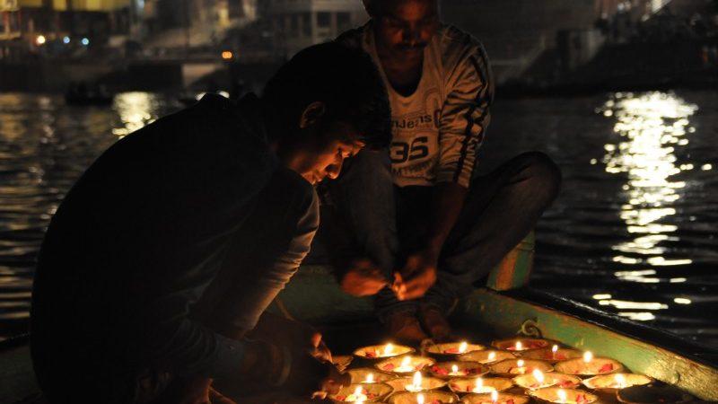 Two men lighting candles in Varanasi