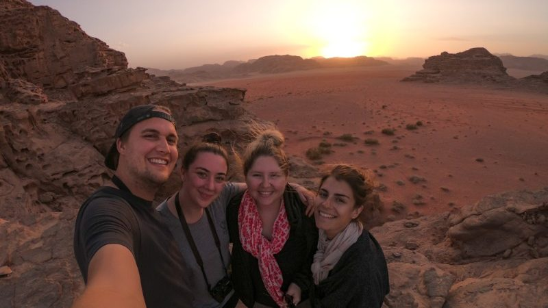 Four travellers taking a selfie in the desert.