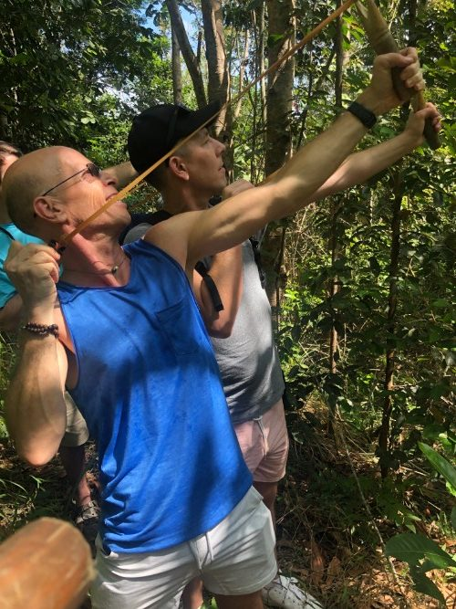 A man holds a slingshot in the jungle
