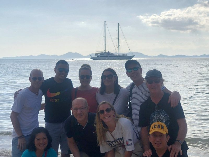 Group photo of travellers with a sailboat in the background