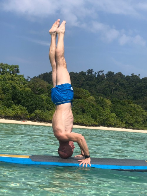 A man does a headstand on a standup paddle board
