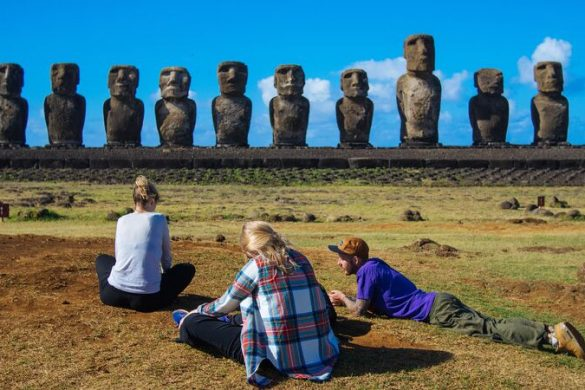 Three travellers sitting in front of the giant stone heads on Easter Island