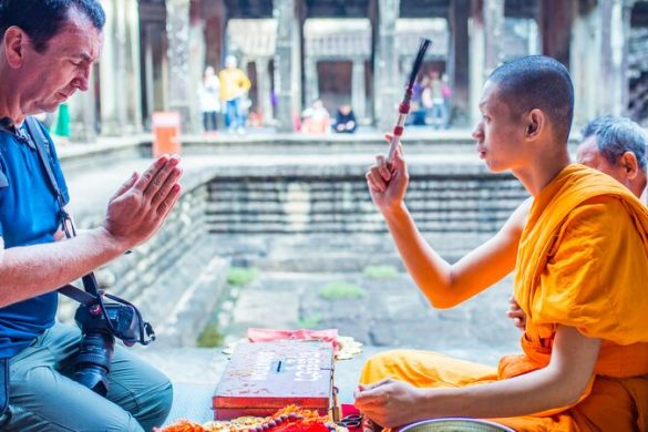 A traveller receives a blessing from a monk in Cambodia