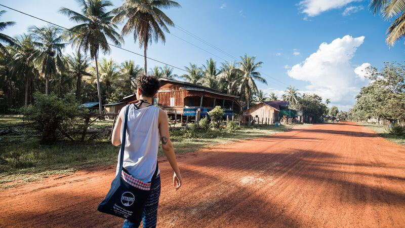 A traveller walks along a dirt road in Cambodia
