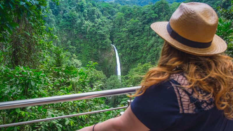 A woman looks over the treetops to a waterfall in Costa Rica