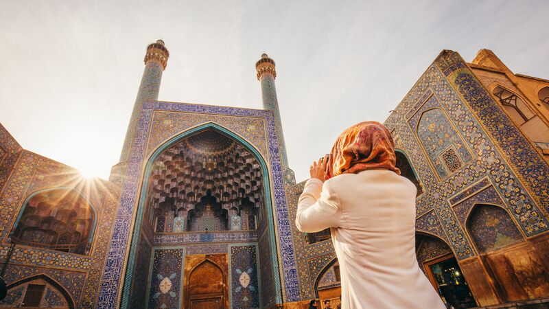 A woman wearing a hijab looking at a temple in Iran
