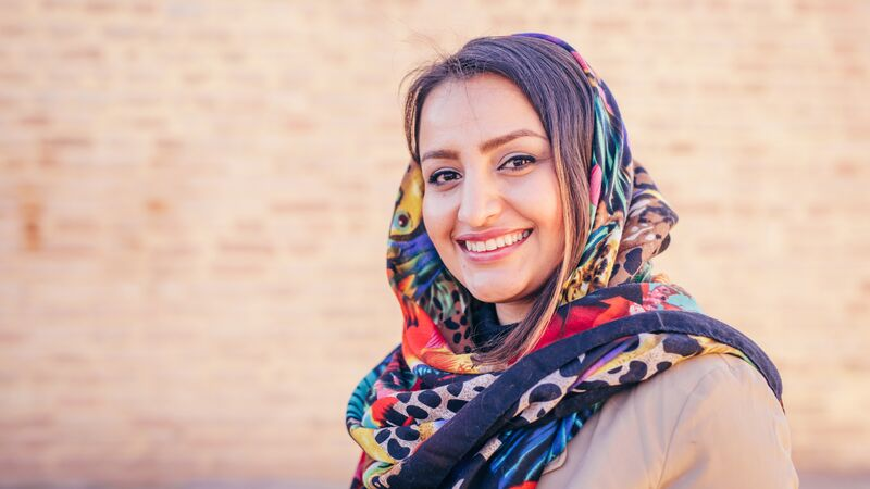 A woman wearing a hijab smiles at the camera