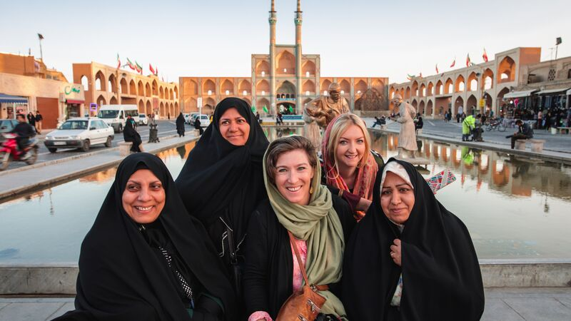 Two travellers pose for a photo with three Iranian locals