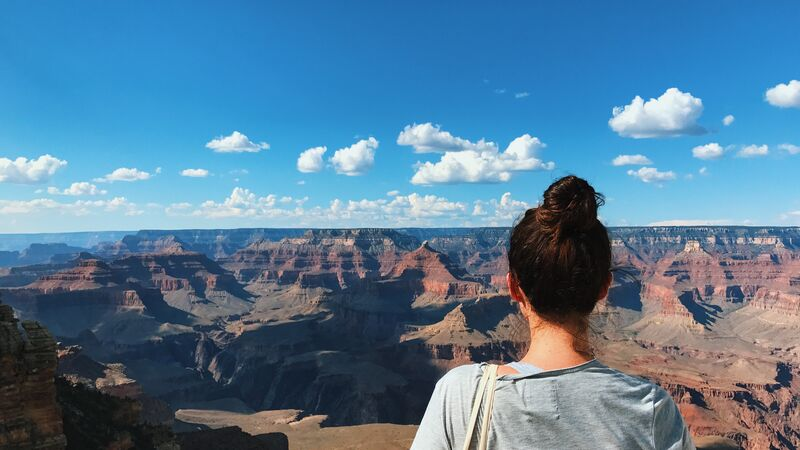 A young woman looks out over the Grand Canyon