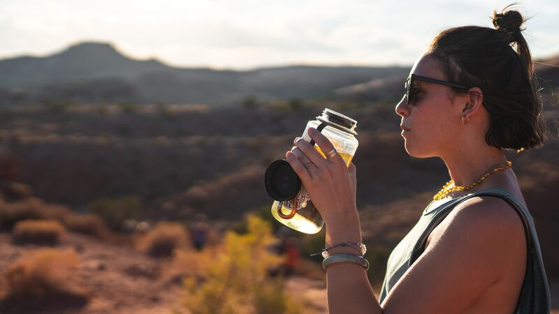 A woman drinking out of a reusable water bottle
