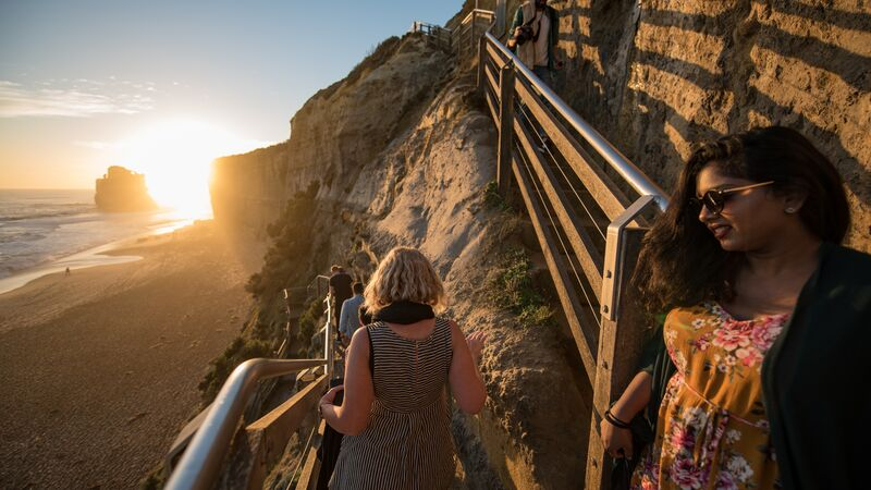 Travellers walking down a staircase to the beach in Australia