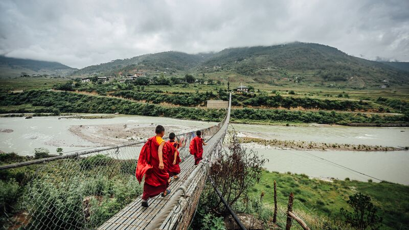 Three monks crossing a bridge in Bhutan