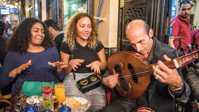 Two girls with a local musician in Cairo