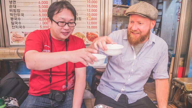 Two men enjoying soup in South Korea