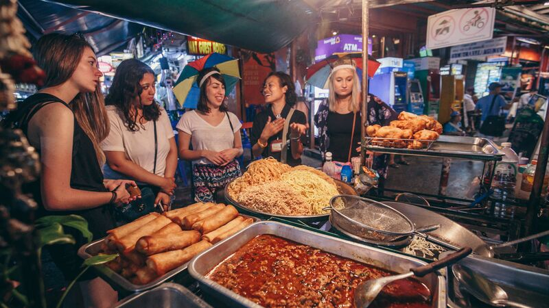Travellers at a street food stall in Thailand