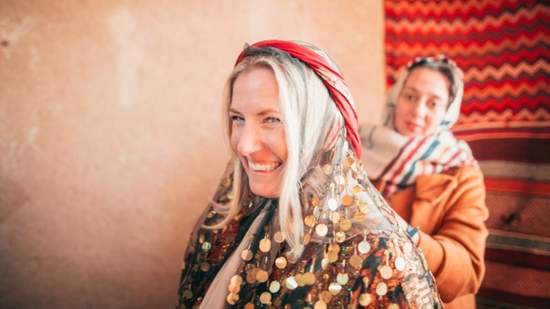 A traveller gets dressed in traditional clothing for a party