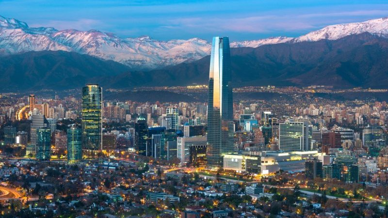 View of a busy city with snow-capped mountains in the background
