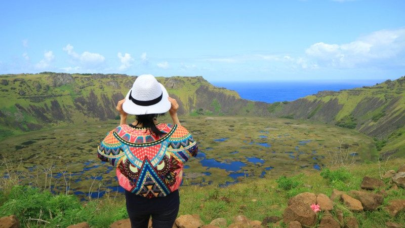 A girl wearing a colourful jumper looks out over a crater on Easter Island