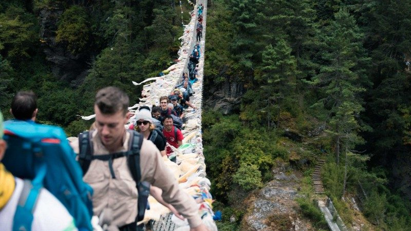 Group of travellers walking along a suspended bridge to Everest Base Camp though forests and shrubs
