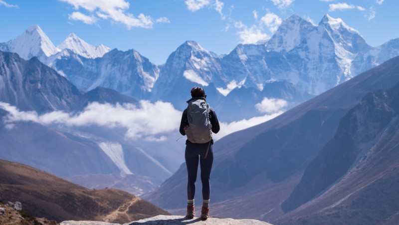 Person standing and overlooking the snowy peaks in Nepal from a high altitude