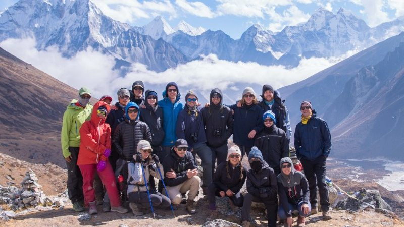Group of travellers together in front of the snowy peaks of Nepal at a high altitude