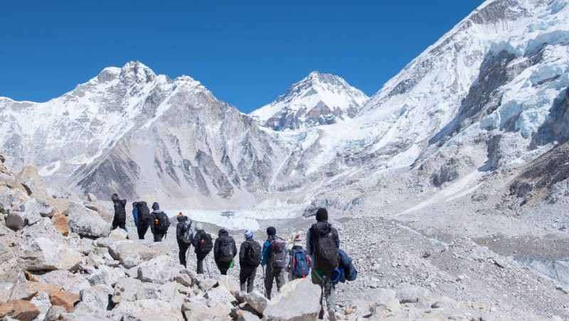 A single line of travellers trek towards the snowy peaks in Nepal