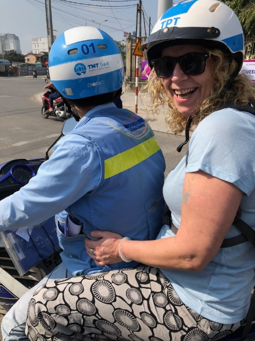 A smiling woman on the back of a motorbike
