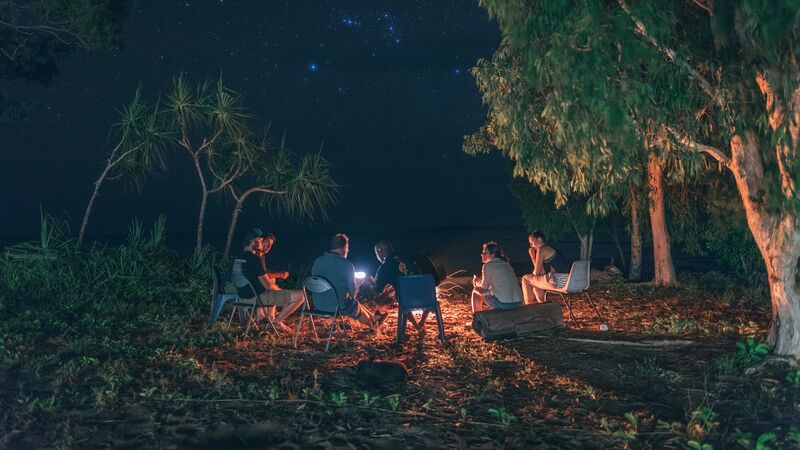 People sitting around a campfire under a starry sky