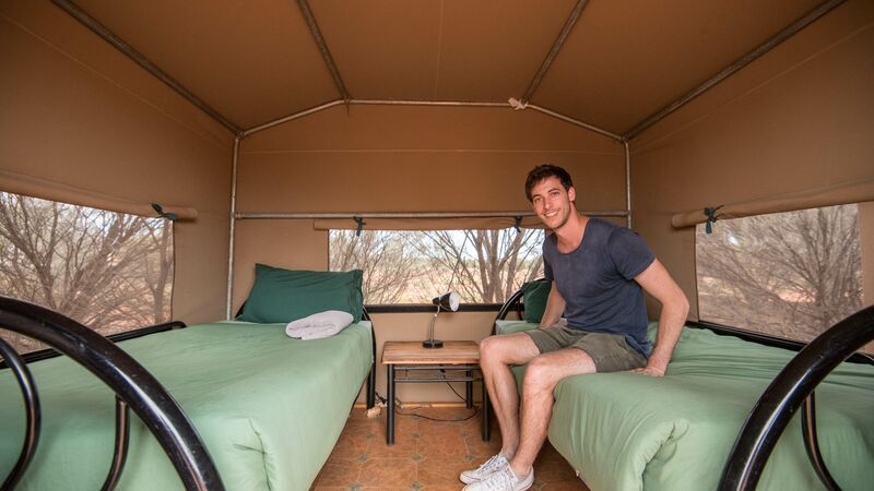 A man sitting in a tent.
