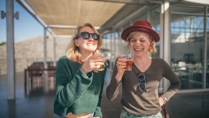 Two women smiling at a brewery.