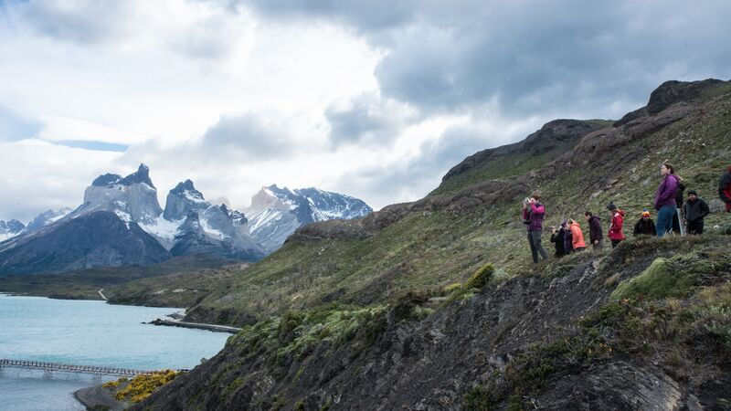 Hikers in Patagonia look out over the lake