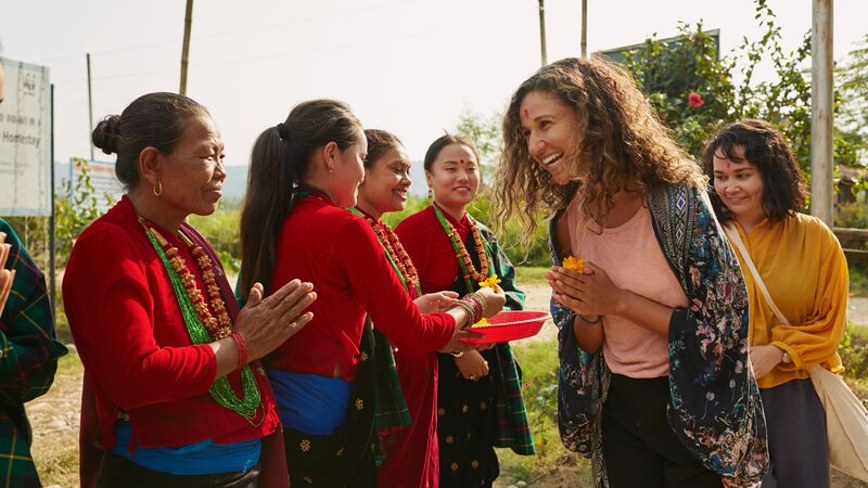 Local women in Nepal meeting two travellers