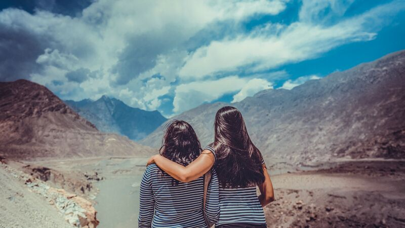 Two women in Pakistan looking over some mountains
