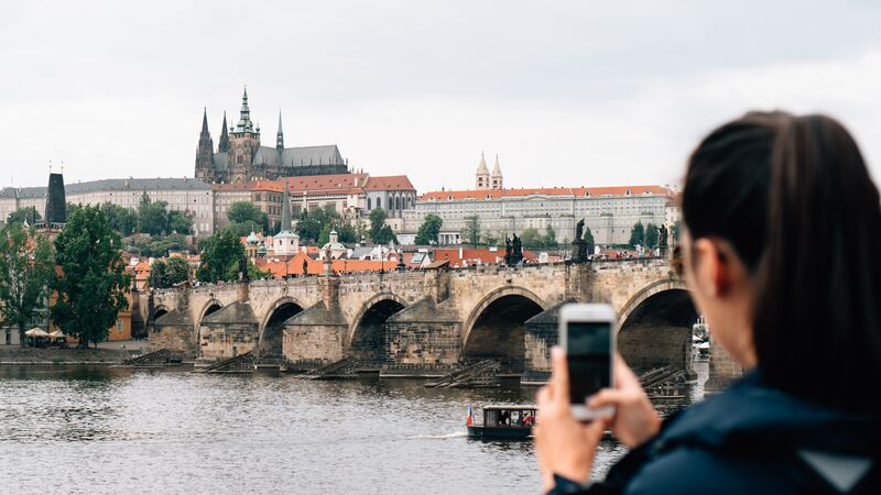 Girl taking a photo on a bridge in Prague.