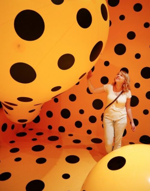 A woman surrounded by enormous orange balls in a gallery.