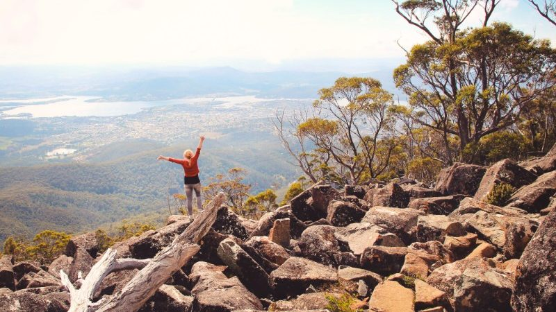 A woman standing at the top of a mountain in a national park in Tasmania