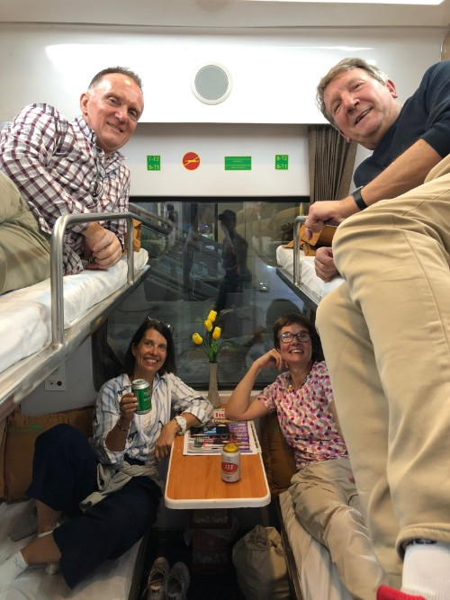 Four travellers in a cabin on an overnight train.