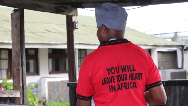 "a man wearing a shirt that says ""you will leave your heart in Africa"" on a Kenya safari"