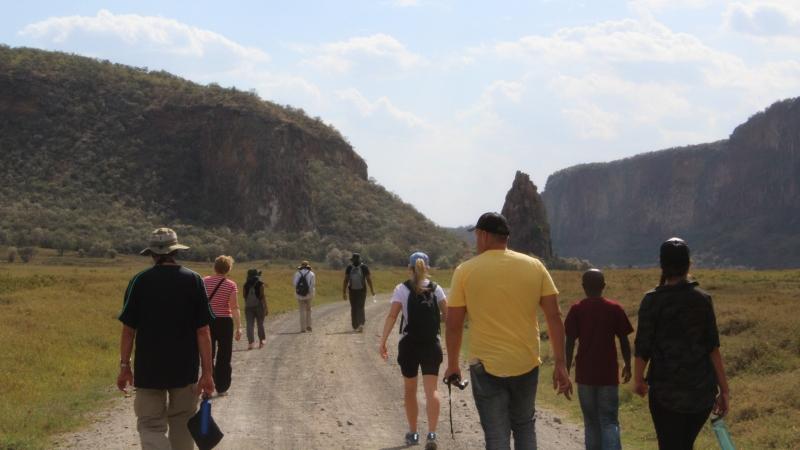 a group of men and women walking through a valley on a Kenya safari