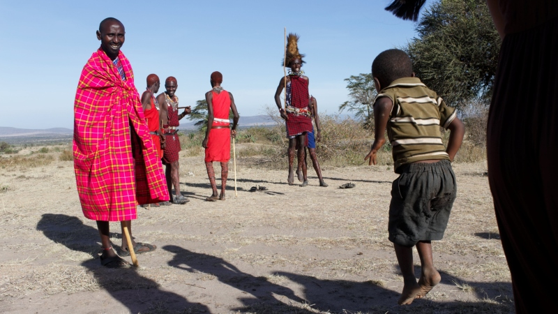 a young boy jumping as high as he can next to a group of men performing the jumping ceremony on a Kenya safari
