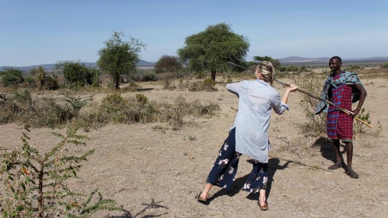 a woman throwing a spear as a Maasai warrior looks at her on a Kenya safari