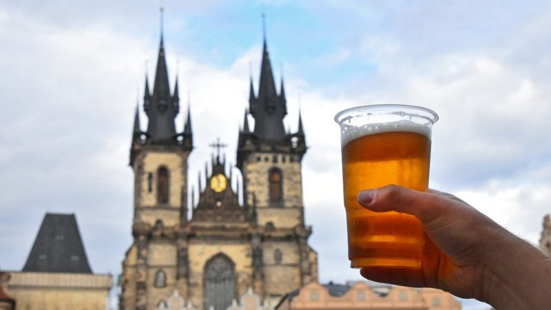 A hand holding up a beer in front of a castle.