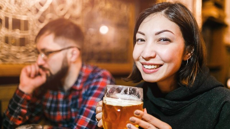 A woman drinking beer in a pub