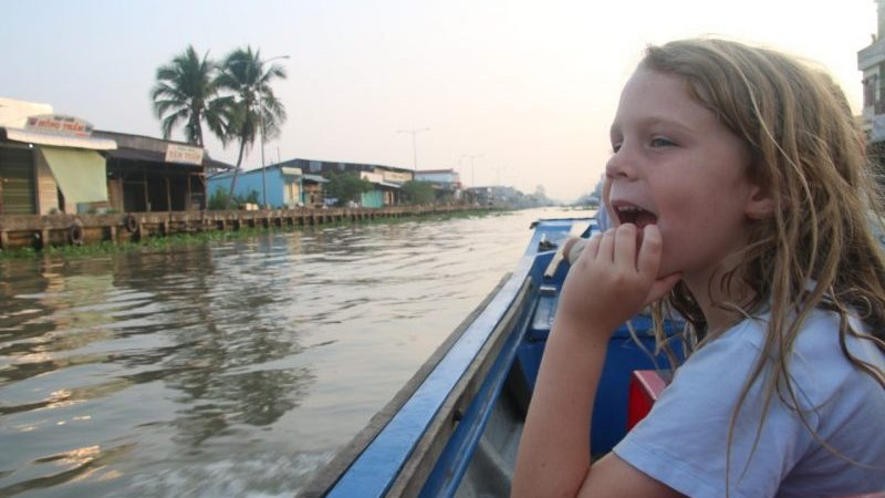 A young boy sitting on a boat in Vietnam