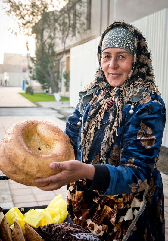 Uzbek woman holding traditional bread.