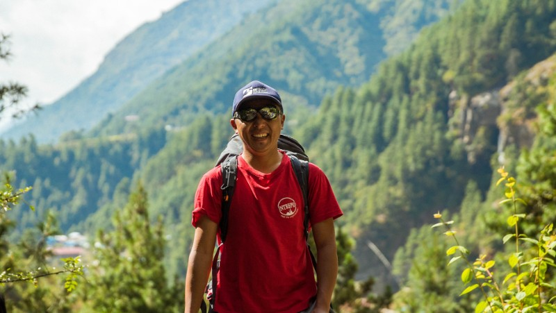 Photo of an Intrepid guide smiling in a red t-shirt with green trees in the background