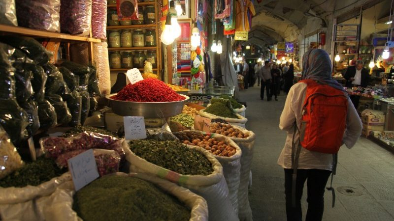 A person walking past sacks full of spices in Iran