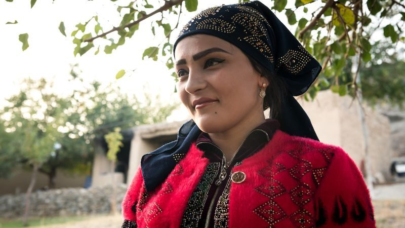A newlywed woman in an Uzbek village smiles for the camera.